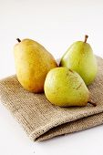 Three pears on rough fabric over white