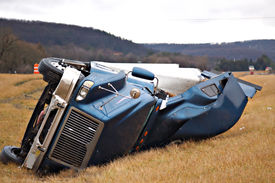 image of tractor-trailer  - A tractor trailer rolls over and lands in the median in this big rig accident - JPG
