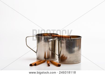 poster of Mulled Wine Or Hot Beverage In Metal Mugs With Cinnamon Sticks. Mugs With Mulled Wine Or Hot Drink A