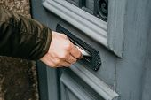 The Postman Puts A Letter Or Newspaper Or Magazine In The Mailbox At The Door Of A Residential Build poster