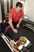 stock photo of chiropractic  - Chiropractor adjusting a female patients neck on a chiropractic bench - JPG