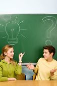 Two students with light bulb and question mark on chalkboard