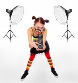 Funny picture of a young photographer woman with old camera in studio.