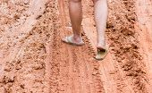 Focused At Leg At Foot With Sandals Walking On  Muddy Road poster
