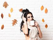 Hot Drink And Club Concept. Girl With Serious Face Holds And Drinks Cup Of Coffee On White Brick Wal poster
