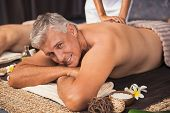 Senior man relaxed in spa while having a back massage. Happy mature man feeling relaxed and looking  poster