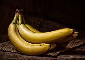 Yellow Bananas On A Wood Table poster