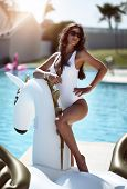 Young Fashion Woman Relaxing In Luxury Swimming Pool Resort Hotel On Big Inflatable Unicorn Pegasus  poster