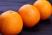 Close Up Three Ripe Orange Fruits. Fresh Healthy Oranges On Dark Wooden Surface. Benefits Of Eating  poster