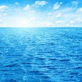 Blauer Himmel mit Sonne über Wasser.