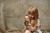 Portrait Of A Little Girl With Long Matted Hair And In Shabby Clothes Playing With Stray Kitten Sitt poster