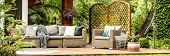 Panorama Of Wicker Garden Furniture With Cozy Pillows And Blankets On A Wooden Terrace In Beautiful poster
