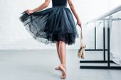 Cropped Shot Of Ballerina In Black Tutu Holding Pointe Shoes In Ballet Studio poster