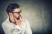 Adult Bearded Man Having Panic And Phobia Looking Away While Biting Nails In Anxiety On Gray Backgro poster