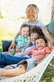 Chinese Grandparents In Hammock with Mixed Race Children. poster