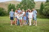 Large family outdoors. Mother, father, children, grandmother, grandfather and dog  poster