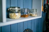 Transparent Jars For Food On White Shelf In The Kitchen. Glass Jars With Lids Close-up poster