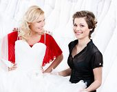 Hesitating about the wedding gown.Shop assistant persuades her