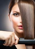 Hairdressing. Hair Straightening Irons.Beautiful Woman with Long Straight Hair. Healthy Hair. Hairst
