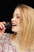 Blonde-haired woman singing against black background