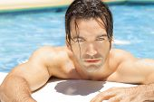 image of good-looker  - Sexy young man in bright blue swimming pool relaxing - JPG