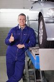 Man standing next to a car with his thumb up in a garage