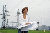 Woman Engineer Or Architect With White Safety Hat Drawings And Electrical Towers Structure On Backgr
