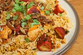 Indian chicken tikka biriyani curry garnished with dried onions and coriander.