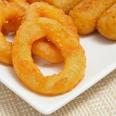 closeup of a plate with spanish croquettes and calamares a la romana, squid rings