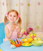 foto of daycare  - Sweet little girl paint Easter eggs on drawing lesson - JPG