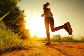 stock photo of wet t-shirt  - Young lady running on a rural road during sunset - JPG