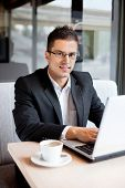 Portrait of smiling man sitting at desk with laptop in cafe, looking at camera