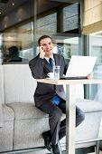 Happy businessman talking on phone in cafe