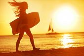 Summer woman body surfer beach fun at sunset. Body surfing girl walking in sunshine in warm evening