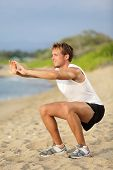 Fitness man training air squat exercise on beach outside. Fit male exercising crossfit outside. Youn