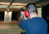 stock photo of shooting-range  - Young man at gun range shooting a glock.