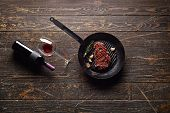 stock photo of bbq food  - Marbled beef steak in a grill pan with a bottle of wine and wine glass on old wood background - JPG