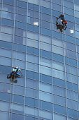 Two man cleaning windows on a high rise building