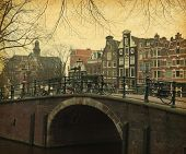 Typical houses behind the bridge in Amsterdam, Netherlands.  Photo in retro style. Paper texture.