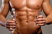 Shaped and healthy body man holding mineral water glass and bottle.