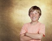 Smiling adolescent with a happy gesture on a over ocher irregular background