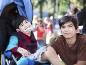 foto of babysitting  - Big brother taking care of disabled little boy in wheelchair outdoors - JPG