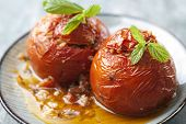 two tomatoes stuffed with rice and cooked in the oven with olive oil