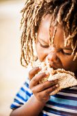 image of rasta  - young african boy with rasta dreadlocks endulging himself in a cold meat sandwich - JPG