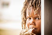 picture of rasta  - young african boy with rasta dreadlock hair biting down on a cold meat sandwich - JPG