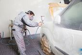 stock photo of labourer  - Car body painter spraying paint or color on bodywork in a garage or workshop with an airbrush - JPG