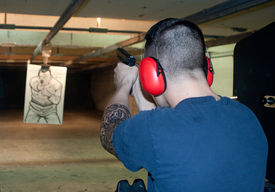 foto of shooting-range  - Young man at gun range shooting a glock.