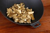 image of gold panning  - Gold pan with golden nuggets inside on wooden background - JPG