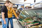 Smiling couple selecting meat from display cabinet at butcher's shop