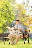 Senior gentleman with hat sitting on a bench and reading a newspaper in a park